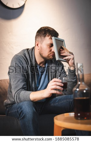 depressed man covering face with photo frame while holding glass of whiskey