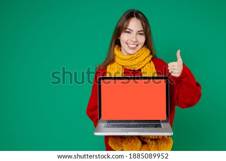 Funny young brunette woman 20s in basic knitted red sweater yellow scarf hold laptop pc computer with blank empty screen showing thumb up isolated on bright green color background studio portrait