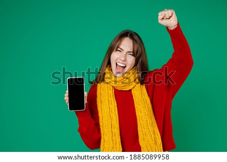 Overjoyed young brunette woman 20s in basic knitted red sweater yellow scarf hold mobile phone with blank empty screen doing winner gesture isolated on bright green color background studio portrait