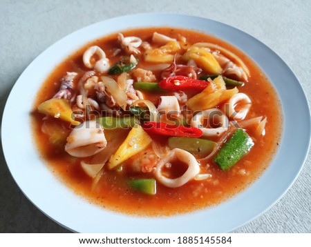 Half Picture of White Plate With Delicous Sweet and Sour Squid and Vegetables. Selective Focus