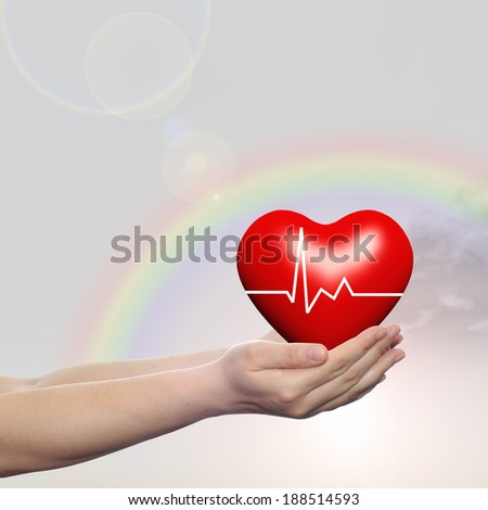 Concept conceptual 3D red human heart sign or symbol held in human man or woman hands, rainbow sky background, metaphor to health, care, medicine, protect, life, medical, pulse, healthcare cardiology #188514593