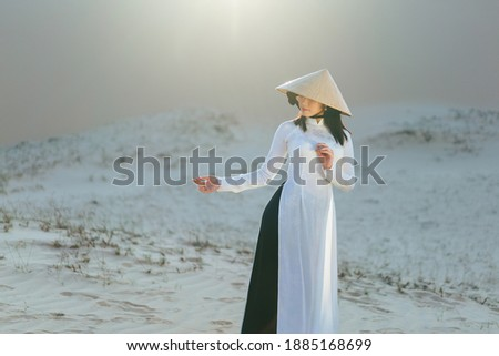 Beautiful vietnamese lady with vietnam culture traditional dress standing at a white sand Mui ne, Ho Chi Minh City Vietnam Royalty-Free Stock Photo #1885168699