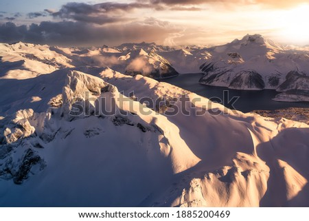 Beautiful aerial landscape view of snow covered mountain, Black Tusk, with a colorful sunset sky. Taken in Garibaldi, near Squamish and Whistler, North of Vancouver, British Columbia, Canada. Royalty-Free Stock Photo #1885200469
