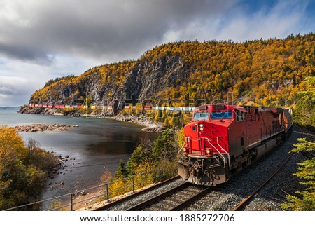 A freight train hauls shipping containers through the rugged landscape. Royalty-Free Stock Photo #1885272706