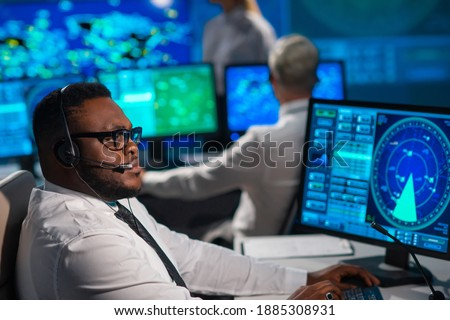 Workplace of the air traffic controllers in the control tower. Diverse team of aircraft control officers works using radar, computer navigation and digital maps. Aviation concept. Royalty-Free Stock Photo #1885308931