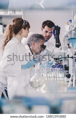 Health care researchers microscoping in life science laboratory. Young research scientists and senior professor preparing and analyzing microscope slides in research lab. Royalty-Free Stock Photo #1885395880