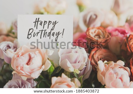 beautiful bright bouquet of colorful roses with white card with the inscription happy birthday, concept of congratulations on the holiday