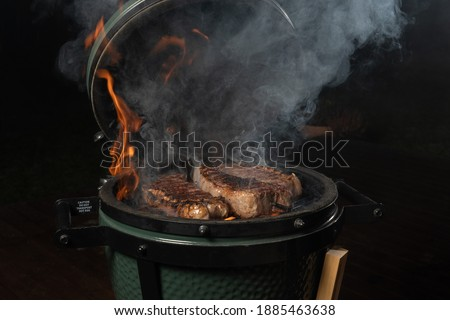 Smoky new york steak on egg type grill. Royalty-Free Stock Photo #1885463638