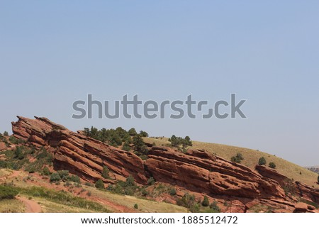 Red sandstone rock formations on grassy hillsides with evergreen treens at Red Rocks State Park in Colorado, USA Royalty-Free Stock Photo #1885512472