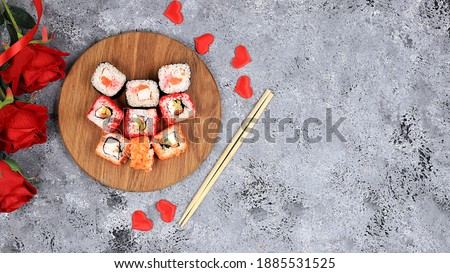 Heart of fresh sushi rolls with roses, valentine's day food, traditional japanese cuisine, place for text, top view, banner for shop advertisement or invitation,