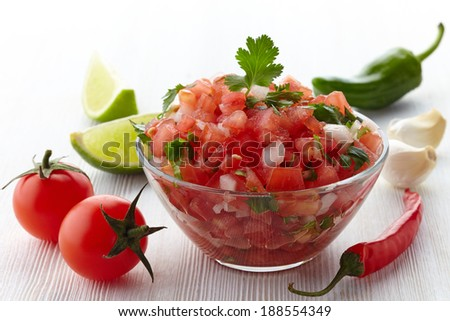 Bowl of fresh salsa dip and ingredients on white wooden background #188554349