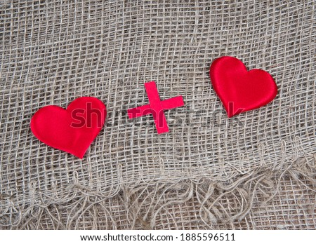 Heart plus heart. Two red toy hearts on natural burlap background, lovers together and forever concept.