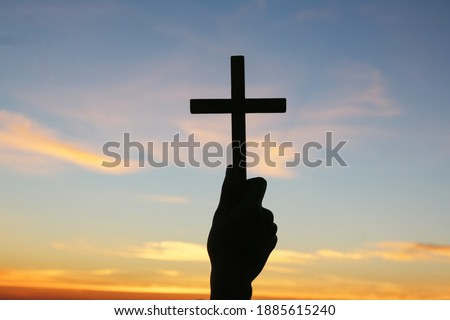 Christian, Christianity, Religion copy space background. Human praying and holding christian cross for worshipping God at sunset background.silhouette Royalty-Free Stock Photo #1885615240