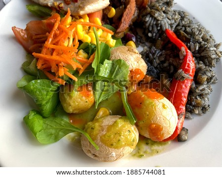 Traditional Canarian potatoes Papas Arrugadas with green and red mojo sauce, green salad leaves on a plate close up Royalty-Free Stock Photo #1885744081