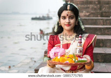 Portrait of beautiful Indian girl in front of ganga river wearing traditional Indian saree, gold jewellery and bangles holding plate of religious offering. Royalty-Free Stock Photo #1885775785