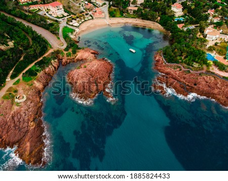 Aerial view of a small beach with turquoise waters, anchored small boat and red rocks, typical of the Esterel close to Cannes. picture taken in Agay, French Riviera, Côte d'Azur south of France