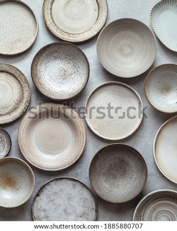 handmade ceramics, empty craft ceramic plates and bowls on light background, top view Royalty-Free Stock Photo #1885880707