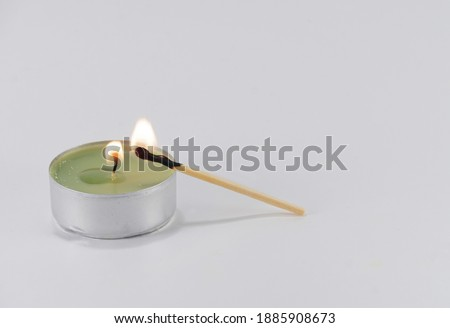Burning candle and a match with which it was lit on a white background. Preparation for the holiday. Royalty-Free Stock Photo #1885908673