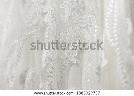 Delicate white wedding dress fabric. Detail close up of lace stitching and embroidery. Royalty-Free Stock Photo #1885929757