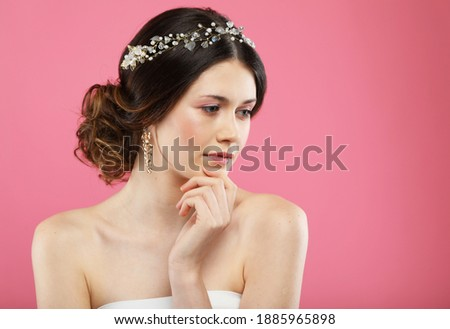 Beautiful young bride with fashion wedding hairstyle, close up picture over pink background
