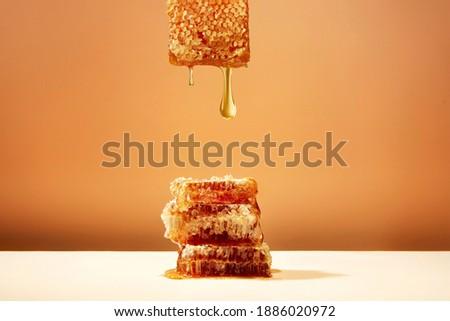honeycomb and honey on yellow background Royalty-Free Stock Photo #1886020972