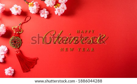 Chinese new year festival decorations made from chinese good luck symbol and plum blossom on a red background.  Flat lay, top view with space. Royalty-Free Stock Photo #1886044288