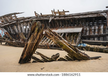 Stranded fishing boats on the beach. Historical wreck in France. Royalty-Free Stock Photo #1886162911