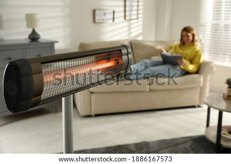 Woman reading book in living room, focus on electric infrared heater Royalty-Free Stock Photo #1886167573