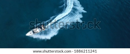 Aerial drone top down ultra wide photo of inflatable power rib boat making extreme manoeuvres in Mediterranean bay with deep blue sea at dusk Royalty-Free Stock Photo #1886211241