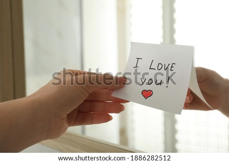 Woman putting sticky note with text I love you! on mirror, closeup