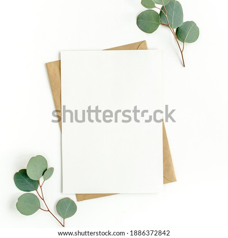 Mockup invitation, blank greeting card and green leaves eucalyptus. Flat lay, top view. Royalty-Free Stock Photo #1886372842