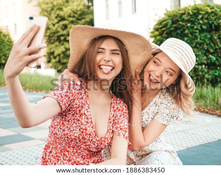 Two young beautiful smiling hipster female in trendy summer sundress.Sexy carefree women posing on the street background in hats. Positive models having fun and hugging. They taking selfie photos