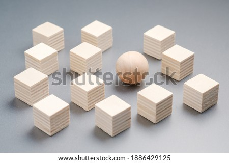 Wooden sphere ball among the wood cubes, different and position in niche market concept Royalty-Free Stock Photo #1886429125