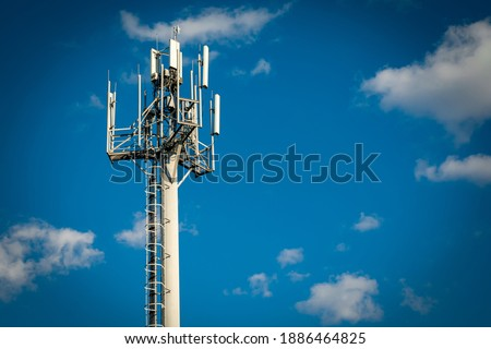 Telecommunication tower with 4G, 5G transmitters. Cellular base station with transmitter antennas on a telecommunication tower on against a blue sky with clouds. Copy space Royalty-Free Stock Photo #1886464825