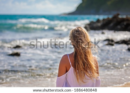 A young beautiful girl looks at the sea, the wind develops her blond hair. White dress, blue water., beautiful view.