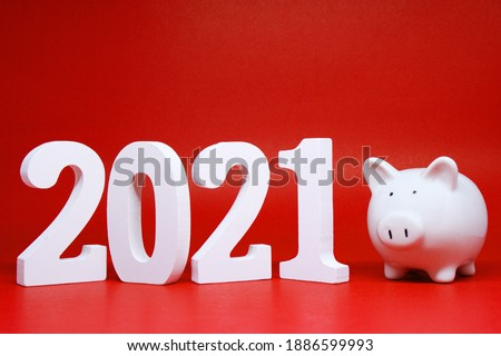 Saving money plan year 2021 for advertising. 2021 wooden word with pink piggy bank on red background studio, Target and start investment and saving of banking and business concept  #1886599993