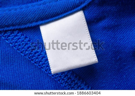 Blank white laundry care clothes label on blue fabric texture background Royalty-Free Stock Photo #1886603404