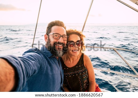 Cheerful people happy adult caucasian couple take selfie picture and enjoy together summer holiday vacation sailing with boat with ocean and sky in background - tourists lifestyle and fun in ocean