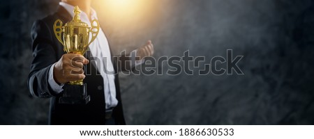 Success and championship leader celebrate concept, successful business man holding prize or cup award  Royalty-Free Stock Photo #1886630533