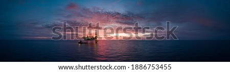 Aerial panorama view from a drone of an offshore jack up rig during sunset time at the offshore location Royalty-Free Stock Photo #1886753455