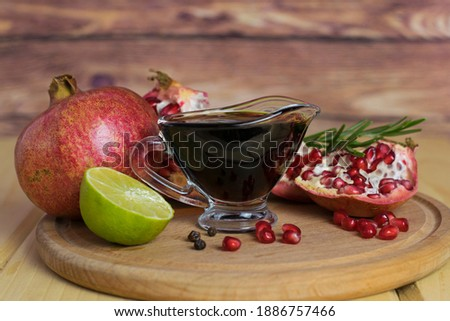 Pomegranate sauce in a gravy boat on a wooden board. Nearby are pomegranate, lime, pomegranate seeds. Narsharab, meat sauce, pomegranate sauce. Royalty-Free Stock Photo #1886757466