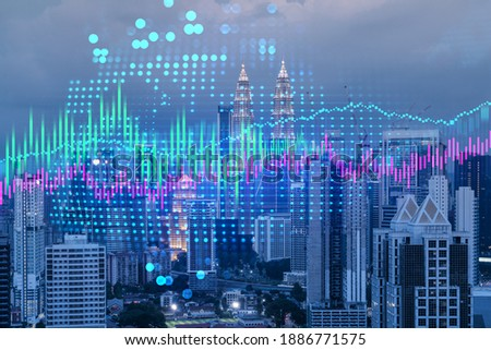 Stock market graph hologram, night panorama city view of Kuala Lumpur. KL is popular location to gain financial education in Malaysia, Asia. The concept of international research. Double exposure. Royalty-Free Stock Photo #1886771575
