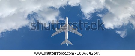 Zoom ultra wide photo of Boeing 747 passenger jumbo jet airplane as seen from ground flying high in deep blue cloudy sky
