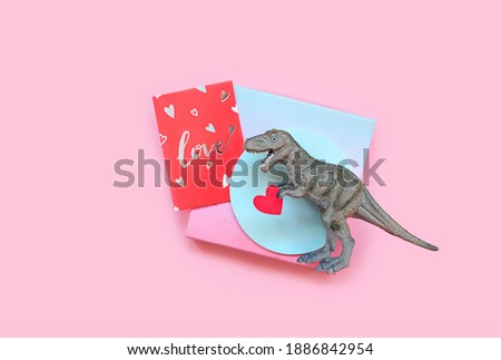 Dinosaur with red heart and greeting love card on pink background. minimal creative concept. symbol of love. Valentine's day, 14 february holiday. romantic gift
