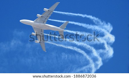 Zoom photo of passenger airplane leaving white smoke trails in deep blue sky while flying at high altitude