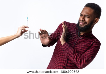No Vaccination. Scared African Man Gesturing Stop To Hand Offering Syringe With Vaccine Refusing To Be Vaccinated Standing Over White Studio Background. Needle Fobia, Fear Of Covid-19 Vaccines Royalty-Free Stock Photo #1886900692