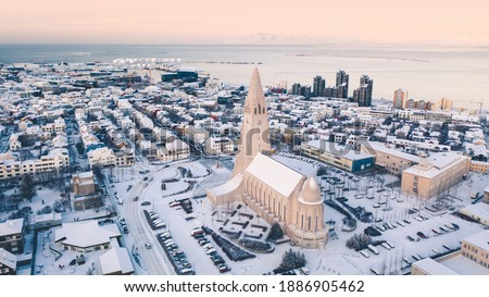 Hallgrimskirkja cathedral church in the center of Reykjavik downtown Iceland. White winter streets covered in snow on the sunset sunrise aerial drone view Royalty-Free Stock Photo #1886905462