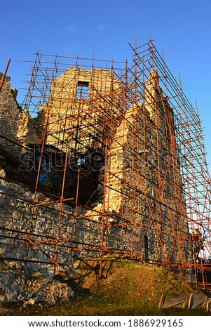 Dense scaffolding on southern walls of medieval Hrusov castle, sunlit by late afternoon winter sunshine. Picture taken during restoration in year 2020.