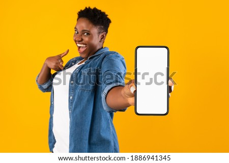 Mobile Application Ad. Excited African Woman Showing Phone Empty Screen Recommending App Standing Over Yellow Studio Background, Smiling To Camera. Cellphone Display Mockup, Check This Apps Royalty-Free Stock Photo #1886941345