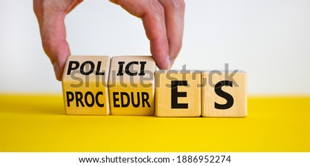 Policies vs procedures symbol. Male hand flips wooden cubes and changes the word 'procedures' to 'policies'. Beautiful yellow table, white background, copy space. Business and policies concept. Royalty-Free Stock Photo #1886952274